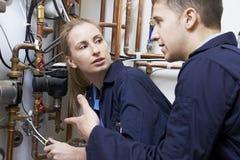 Женский водопроводчик тренирующей работая на боилере центрального отопления стоковое изображение