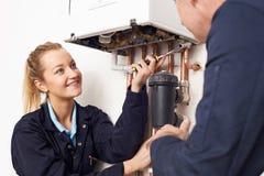 Женский водопроводчик тренирующей работая на боилере центрального отопления стоковая фотография rf