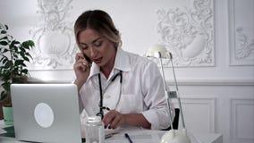 Женский врач говоря на телефоне и смотря документы сток-видео