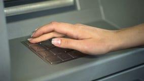 Женский входя в секретный номер для проверки банковского счета и для того чтобы разделить деньги от ATM стоковое фото rf
