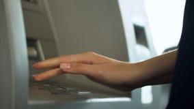 Женский входя в секретный номер для проверки банковского счета и для того чтобы разделить деньги от ATM стоковое фото