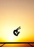 Женский гимнаст на коромысле в заходе солнца Стоковые Изображения