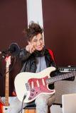 Женский гитарист указывая пока выполняющ в студии стоковое фото