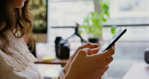 Женский график-дизайнер используя мобильный телефон в современном офисе 4k акции видеоматериалы