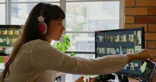 Женский график-дизайнер слушая музыку пока работающ на столе 4k видеоматериал
