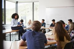 Женский гувернер средней школы сидя на таблице при зрачки уча классу математик стоковые фото