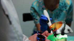 Женский дантист и ее медсестра установили уплотнение к пациенту лежа в стуле зубоврачебного офиса акции видеоматериалы
