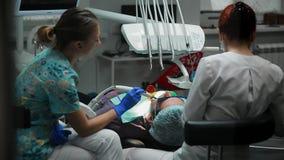 Женский дантист и ее медсестра установили уплотнение к пациенту лежа в стуле зубоврачебного офиса сток-видео