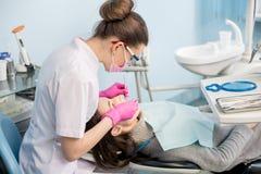 Женский дантист с зубоврачебными инструментами - отразите и прозондируйте обрабатывать терпеливые зубы на зубоврачебном офисе кли стоковая фотография rf