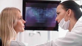 Женский дантист указывая на рентгеновский снимок пациента сток-видео
