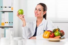 Женский диетолог держа зеленое яблоко стоковые изображения