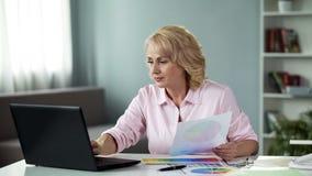 Женский дизайнер работая на проекте на ноутбуке, выбирая цветовую схему на таблице стоковые изображения