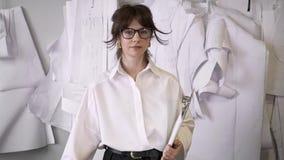 Женский дизайнер с папкой папки доски сзажимом для бумаги смотря камеру видеоматериал