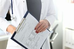 Женский доктор вручает держа и заполняя пациента стоковые фотографии rf