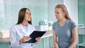 Женский доктор в белом пальто лаборатории обсуждая симптомы при больные жалобы девушки делая диагноз видеоматериал