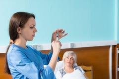 Женский доктор в форме получает готовым сделать впрыску к Стоковые Фотографии RF
