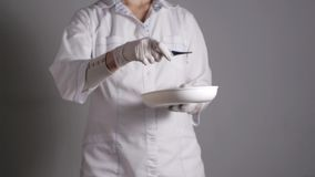 Женский доктор давая лекарство Молодой медицинский профессионал дает цифровой термометр принимая от блюда почки медленно сток-видео