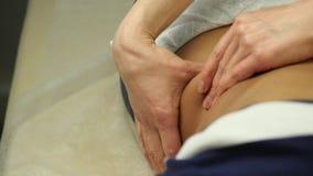 Женский доктор делает подбрюшный массаж к пациенту Массаж Anticellulite в клинике движение медленное акции видеоматериалы