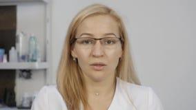 Женский доктор имея видео конференц-связь с пациентом Женщина перед камерой, на-линией медицинскими консультациями акции видеоматериалы