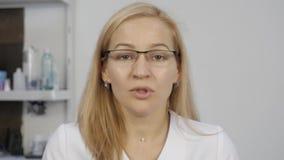 Женский доктор имея видео конференц-связь с пациентом Женщина перед камерой, на-линией медицинскими консультациями видеоматериал
