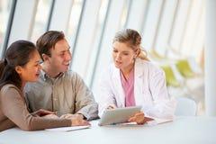 Женский доктор Используя Цифров Таблетка Talking с пациентами стоковые фото