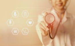 Женский доктор медицины стоя и держа стетоскоп для пациента проверки с значком медицинский Стоковое Изображение