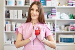 Женский доктор нося розовые перчатки мантии и латекса, имеет длинные прямые каштановые волосы, держит красное пластиковое сердце, стоковое фото