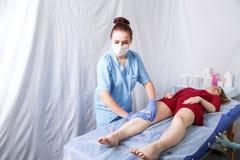 Женский доктор обрабатывает ноги молодой женщины со сливками стоковая фотография rf