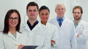 Женский доктор пишет на ее доске сзажимом для бумаги стоковое изображение rf