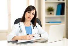 Женский доктор работая со стетоскопом и доской сзажимом для бумаги в медицинском офисе с серьезным выражением стороны стоковое изображение