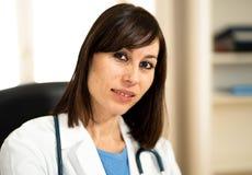 Женский доктор работая со стетоскопом и доской сзажимом для бумаги в медицинском офисе с естественным выражением стороны стоковая фотография