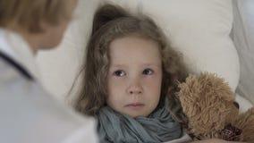 Женский доктор разговаривая при больная плача девушка лежа в кровати дома, здравоохранение видеоматериал