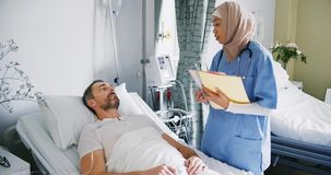 Женский доктор разговаривая с пациентом в больничной койке 4k акции видеоматериалы