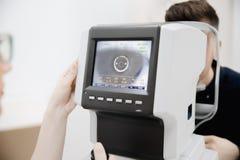 Женский доктор руки держит монитор ophthalmological прибора с индикаторами наблюдает парень зрачка давления и визируя изображения стоковые изображения rf