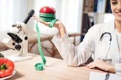 Женский доктор сидя на столе в офисе с микроскопом и стетоскопом Женщина держит красное яблоко с измеряя лентой стоковая фотография rf