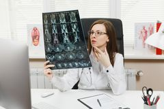 Женский доктор сидя на столе с компьютером, фильмом рентгенизирует мозг радиографическим mri развертки ct изображения в светлом о стоковое изображение