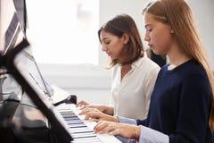 Женский зрачок при учитель играя рояль в уроке музыки стоковые изображения rf