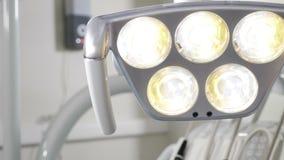 Женский зубоврачебный хирург регулируя освещение перед деятельностью : Крупный план снятый руки хирурга акции видеоматериалы