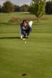 Женский игрок в гольф выравнивая вверх удар, загоняющий мяч в лунку Стоковое фото RF