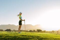 Женский игрок в гольф стоя на поле для гольфа Стоковое Изображение RF