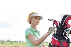 Женский игрок в гольф с сумкой гольф-клуба против ясного неба Стоковые Изображения RF