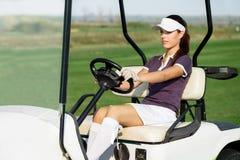 Женский игрок в гольф управляя тележкой гольфа стоковые изображения rf