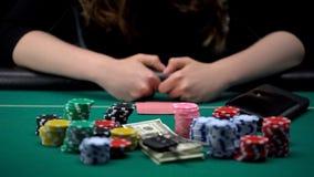 Женский игрок в покер держа пари все обломоки, деньги и ключи дома на игре казино стоковая фотография
