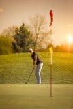 Женский игрок гольфа кладя на заход солнца Стоковое Изображение
