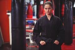 Женский игрок карате выполняя позицию карате стоковые изображения