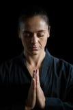Женский игрок карате в представлении молитве стоковые фотографии rf