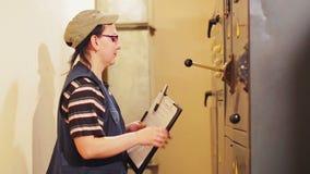 Женский инженер идя к электрическим панели и показателям чтения приборов в коммутаторе акции видеоматериалы