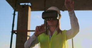 Женский инженер нося строительный проект шлемофона VR управляя видеоматериал