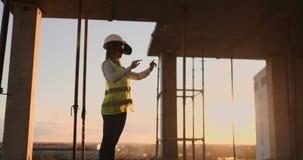 Женский инженер нося строительный проект шлемофона VR управляя сток-видео