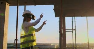 Женский инженер нося строительный проект шлемофона VR управляя акции видеоматериалы